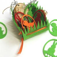 Подарочная композиция изготовлена из фетра толщиной 3 мм. Использовано сочетание прорезных элементов и гравировки логотипа. Яйца для декорирования корзинки изготовлены из фетра, дерева и вспененной резины. Элементы снабжены ленточками-завязками. В корзинку можно добавить пасхальные яйца, сладости, подарки. Корзинки с легкими подарками можно подвесить.